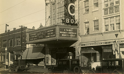 Photo of the Music Box Theatre exterior in 1929 with cars of that time perior parked on the street.