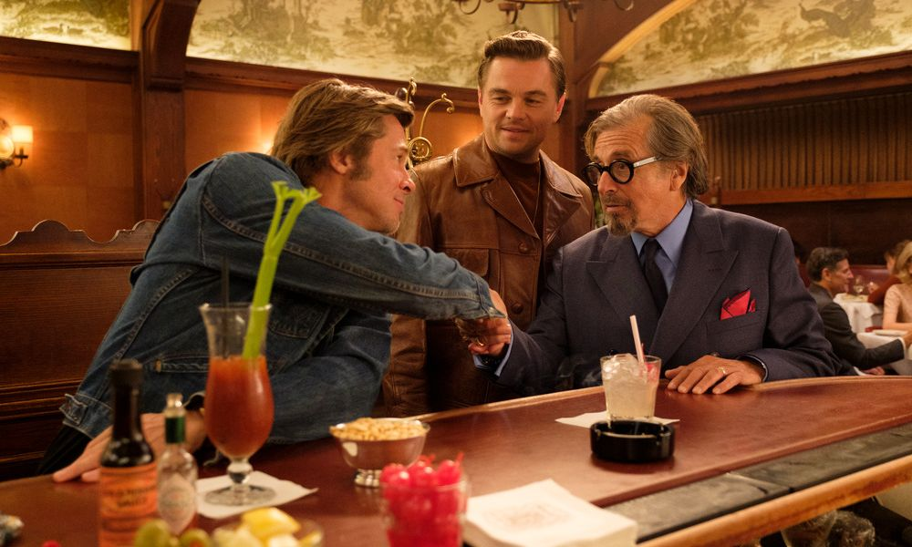 Two men shaking hands with another man standing behind them in Once Upon a Time in Hollywood