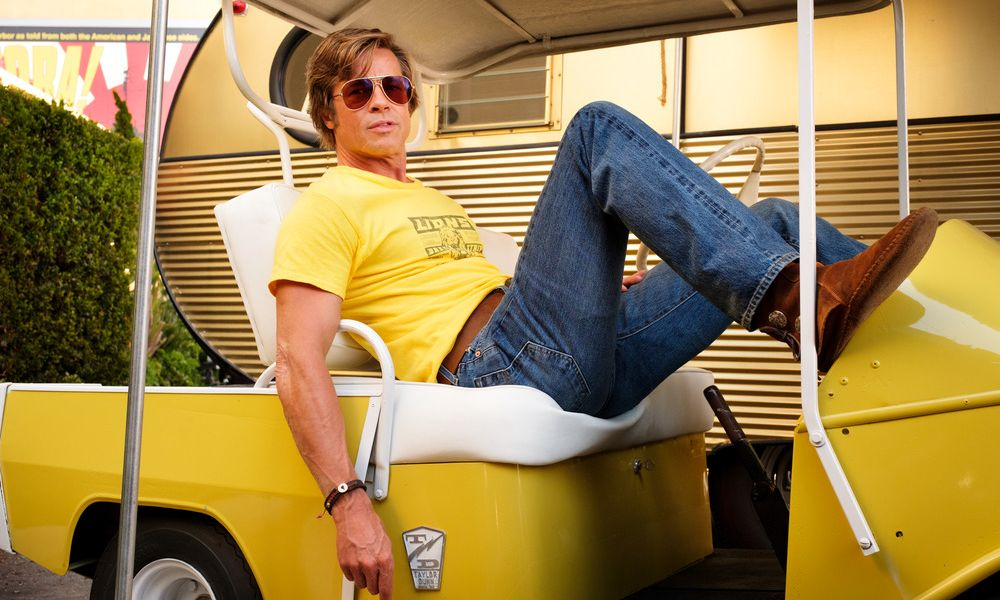 Man in yellow shirt sitting on a yellow golf cart in Once Upon a Time in Hollywood