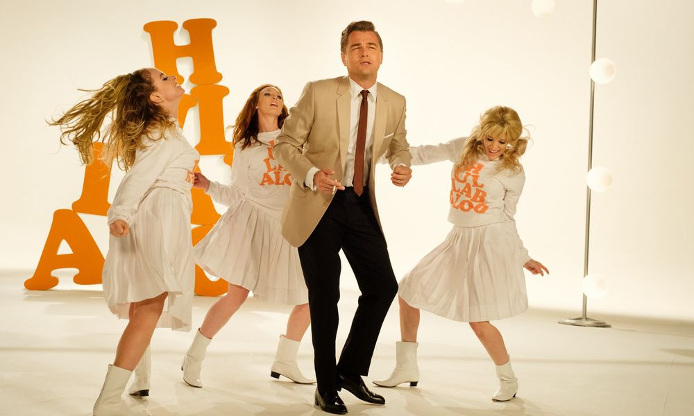 Man dancing in leisure suit with women dancers in background in Once Upon a Time in Hollywood
