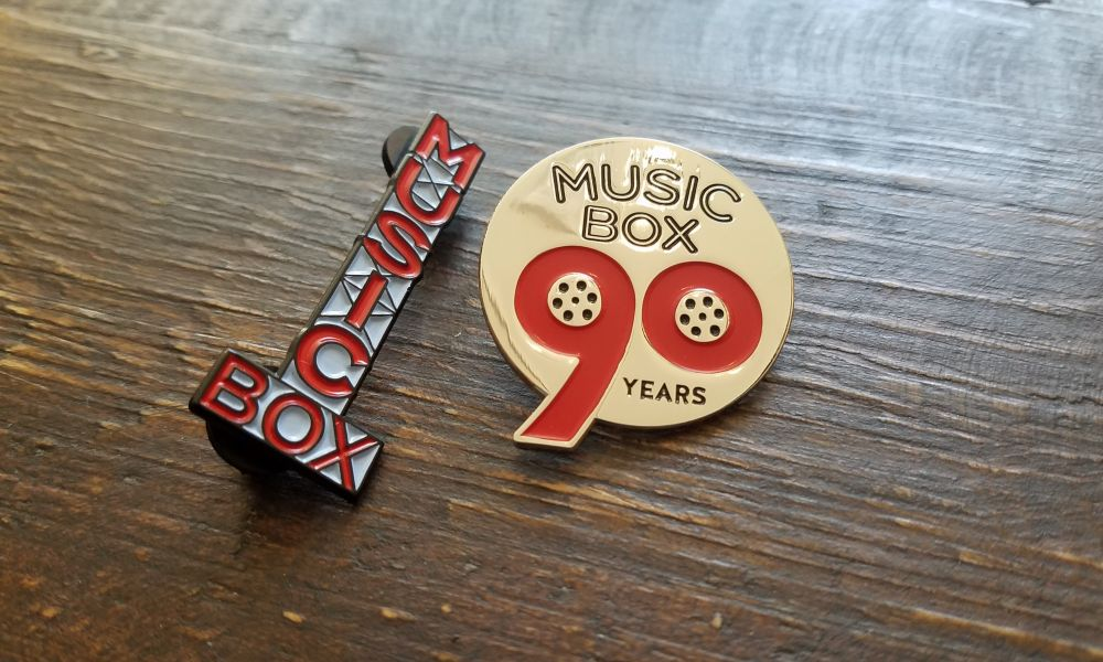 Music Box Marquee enamel pin and 90 Years enamel pin.